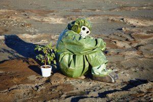 homme assis dans la mer polluée